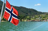 picture of fjord  - A Norwegian flag on the car ferry from Solvorn to Urnes on the fjord with Solvorn in the background in Sogn og Fjordane Norway - JPG