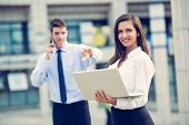 foto of business-partner  - Young business partners standing in front of the building - JPG