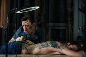 stock photo of freaky  - Freaky tattoo master makes funny faces in his studio - JPG