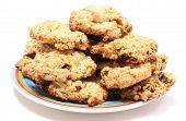 stock photo of baked raisin cookies  - Closeup of oatmeal cookies with raisins and hazelnut lying on colorful plate - JPG