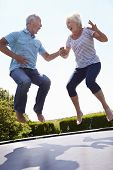 picture of bouncing  - Senior Couple Bouncing On Trampoline In Garden - JPG