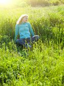 picture of knitted cap  - Portrait of young beautiful girl in a knitted cap in a grassy field at sunset.