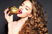 foto of bread rolls  - Cute pretty young girl with curly hair and bright pink lips holding golden bread roll near face standing with closed eyes and open mouth on dark grey background horizontal picture - JPG
