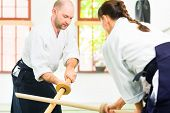 pic of aikido  - Man and woman fighting with wooden swords at Aikido training in martial arts school  - JPG