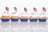 foto of sprinkling  - Row of patriotic 4th of July cupcakes with sprinkles and American flags - JPG