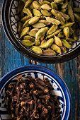 foto of cardamom  - two ceramic bowls full of cardamom and cloves - JPG