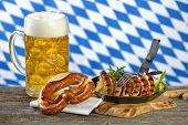 image of pretzels  - Fried Nuremberg sausages on sauerkraut with a mug of Bavarian beer and a pretzel - JPG