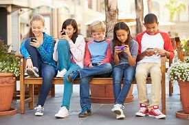 pic of pre-adolescents  - Group Of Children Sitting In Mall Using Mobile Phones - JPG