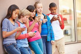 stock photo of pre-adolescents  - Group Of Children Sitting In Mall Using Mobile Phones - JPG