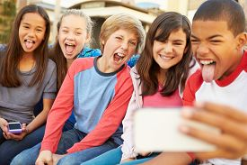 picture of pre-adolescents  - Group Of Children Sitting On Bench In Mall Taking Selfie - JPG