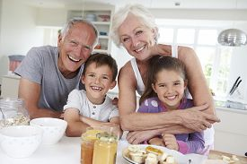 stock photo of grandparent child  - Grandparents With Grandchildren Eating Breakfast In Kitchen - JPG