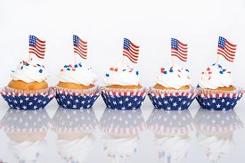 picture of sprinkling  - Row of patriotic 4th of July cupcakes with sprinkles and American flags - JPG