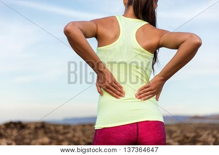 Trail running runner with painful lower back pain injury or strained muscle near the spine. Female a
