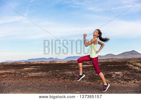 Funny runner athlete goofy woman having fun jogging on outdoor mountain nature trail. Running fitnes