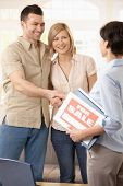 stock photo of real-estate agent  - Happy couple making deal with estate agent - JPG