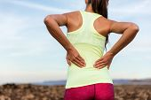 Trail running runner with painful lower back pain injury or strained muscle near the spine. Female a poster