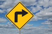 picture of traffic sign  - Left turn traffic sign with clouds in the background - JPG
