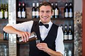Portrait of bartender pouring tequila into shot glass at bar counter in bar poster