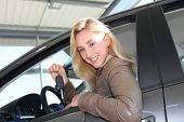 Smiling woman holding brand new car key poster