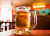 Drinking Beer In Daytime. Transparent Glass Mug With Beer On Wooden Table. Lunch In Cafe With Beer.  poster