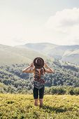 Stylish Traveler Girl In Hat Looking At Sunny Mountains. Summer Vacation. Travel And Wanderlust Conc poster