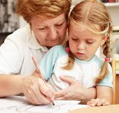 stock photo of nana  - Grandma and grand daughter painting together  - JPG