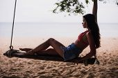 Traveler Woman Relaxing On Wooden Swing. Young Fashion Woman Relax On The Beach. Happy Island Lifest poster