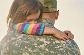 Little Female Child Is Hugging A Soldier. Close Up Portrait Of Happy Girl Is Hugging Her Father In M poster