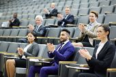Happy audience clapping hands after speech or presentation of colleague at business conference poster