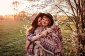 Middle-aged Mother And Her Adult Daughter Hugging In Blooming Garden. Mothers Day Concept. Family V poster