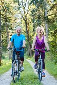 Full length of a happy and active senior couple wearing cool fitness outfits while riding bicycles o poster