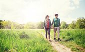 travel, hiking, backpacking, tourism and people concept - happy couple with backpacks holding hands  poster