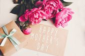 Happy Mothers Day Text On Craft Card And Pink Peonies Bouquet With Gift Box On Rustic White Wooden  poster