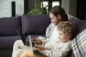 Curious Smiling Child Typing On Laptop Looking At Screen With Dad On Sofa, Daddy And Little Boy Usin poster