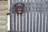 Brown Metal Mailbox On Grey  Natural Aged Wooden Fence. poster