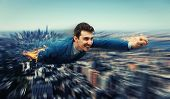 Happy, Smiling Businessman Flying Over The City Skyscapers Like A Superhero. Huge Speed With Motion  poster