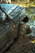 Fragment Of Car Stuck In Dirt, Close Up. Dangerous Expedition Concept. Offroad Tire Covered With Mud poster