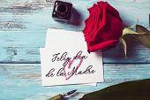 a red rose, an ink bottle, a nib pen and a piece of paper with the text feliz dia de la madre, happy poster