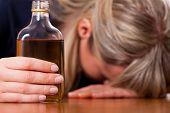 Постер, плакат: Женщина сидя у себя дома пить слишком много алкоголя коньяк она пристрастилась