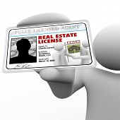 A real estate agent holds a laminated license proving he is certified and licensed by the proper aut
