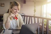 Pretty Young Woman Shopping Online Using Her Credit Card And Laptop Computer. Smiling Blonde Woman M poster