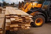 Forklift loads the boards in the lumber yard poster