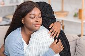 Hypocrisy In Friendship Concept. Afro Girl Hugging Upset Friend With Sneaky Face Expression, Sitting poster