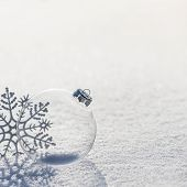 Winter Background With Transparent Glass Ball And Silver Snowflakes On Whiteness Snow Surface. Merry poster