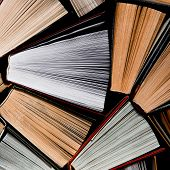 Lots Of Colourful Thick Open Books Stand On A Dark Background poster