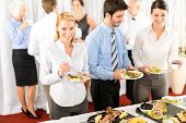 stock photo of buffet lunch  - Business colleagues serve themselves at buffet catering service company event - JPG