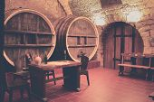 Old Oak Barrels In An Ancient Wine Cellar. Ancient Wine Cellar In The Ancestral Castle For Wine Tast poster