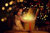 Magic for Christmas. Happy excited little girl opens a box with gifts and surprises. Beautiful Chris poster