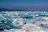 Large Ice Hummocks Of Transparent Ice On Lake Baikal. The Ice Is Green And Blue. Mountains On The Ho poster