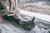 Woman sitting by the window reading book drinking coffee. Winter snowing landscape outside  poster